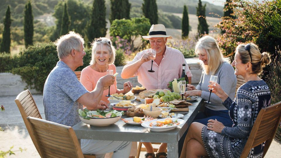 A group of mature friends are sitting around an outdoor dining table, eating and drinking.