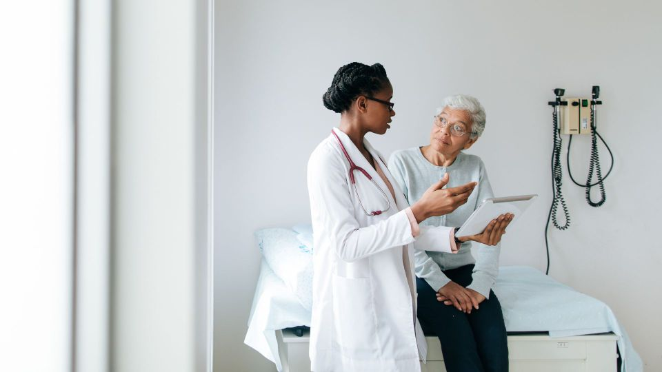 A young female doctor explaining to a senior female patient using a digital tablet in a hospital room.