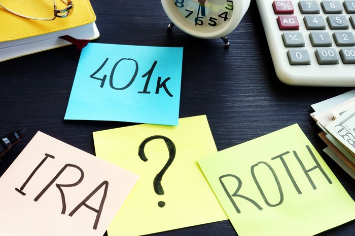 Desktop with sticky notes labeled as 401k, Roth, and IRA.