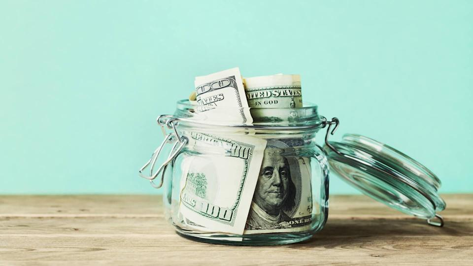 Dollar bills in glass jar on wooden table.