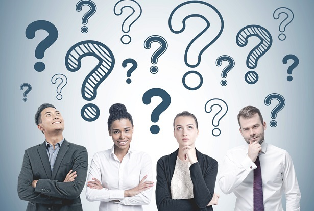 four male and female professionals looking up at question marks