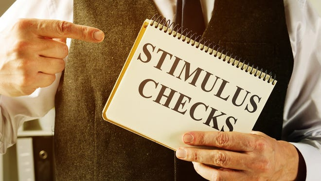A man holds information about stimulus checks.