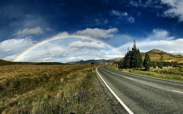 Road leading to a rainbow