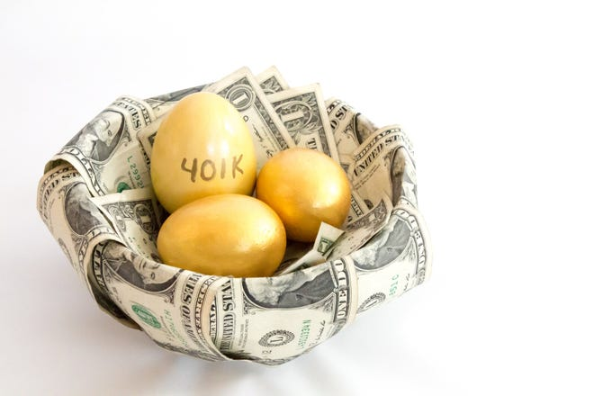Gold eggs, with one marked 401(k), in a basket of dollar bills.