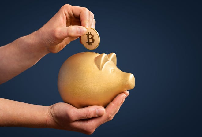 A person puts a coin with the Bitcoin logo in a piggy bank.