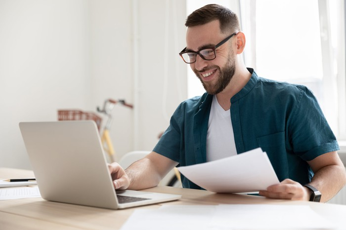 Smiling person at laptop holding papers in hand