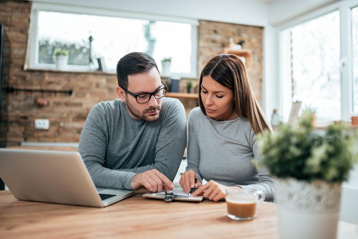 Couple reviewing papers in front of laptop