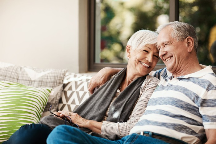 A senior couple sitting on the couch and smiling.