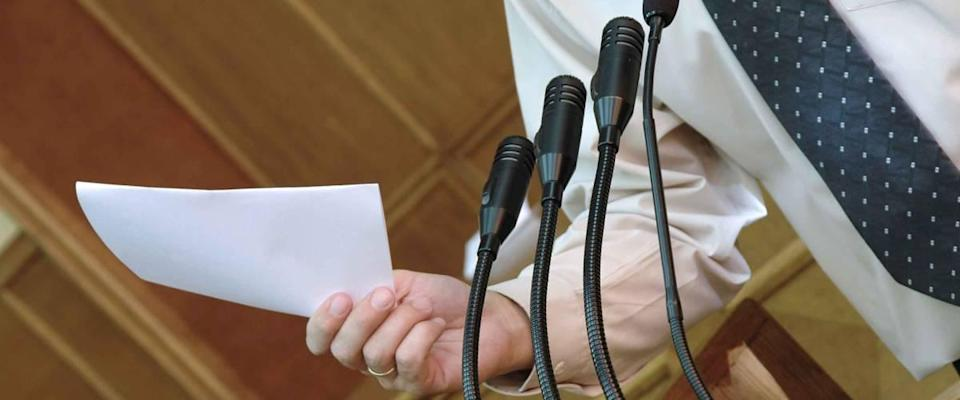 Man stands in front of several microphones, close up and talking while holding piece of paper.