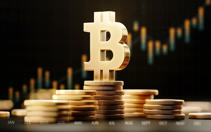 Bitcoin symbol on top of stacks of gold coins