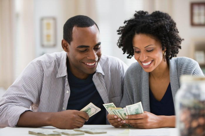 Two smiling people counting money.