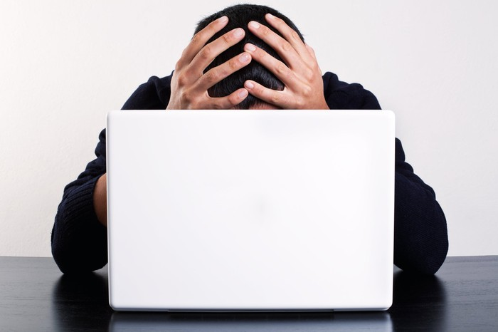 Person at laptop with hands on top of head.
