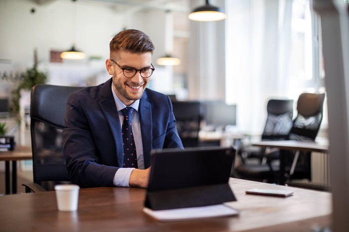 Smiling person in suit using laptop at desk.