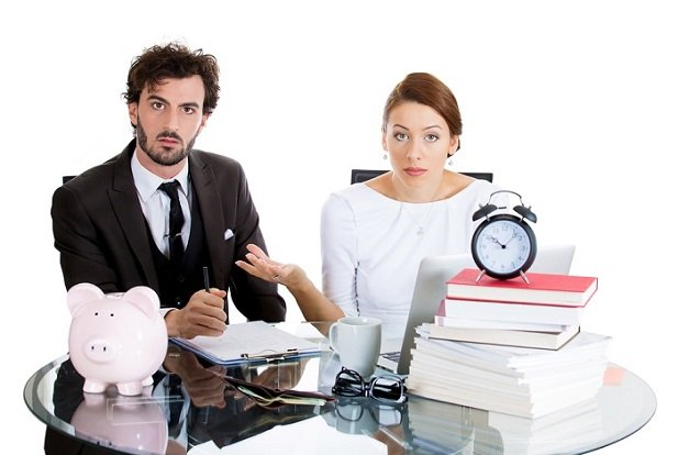 man and woman sitting with calculator looking stunned