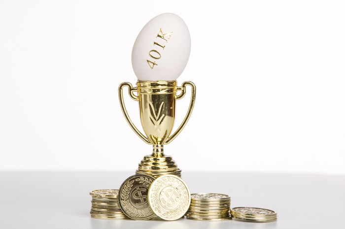 Egg with 401k written on it inside a trophy with gold colored coins
